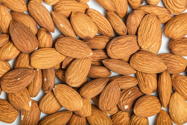 Background of big raw peeled almonds situated arbitrarily. top view. macro photography
