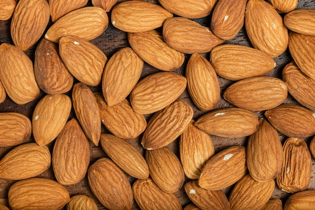 Background of big raw peeled almonds situated arbitrarily. top view. macro photography.