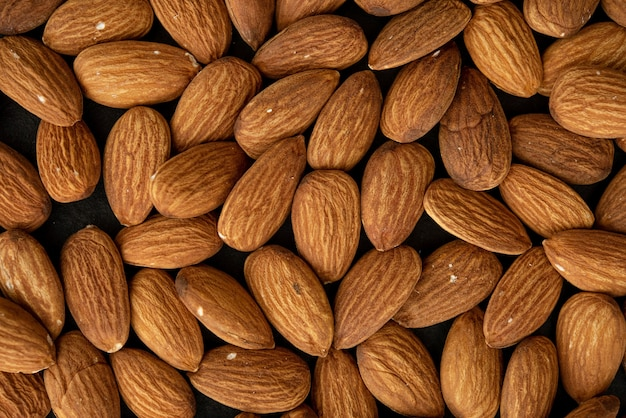 Background of big raw peeled almonds. top view.