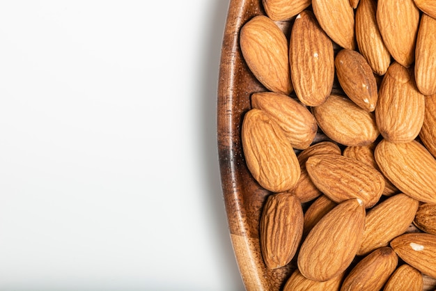 Background of big raw peeled almonds in a wooden bowl. tip view.