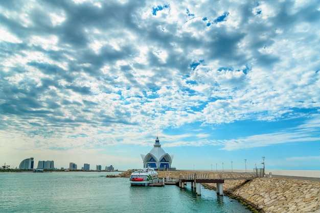 Background of blue sky with beautiful clouds and azure sea with marina in the frame