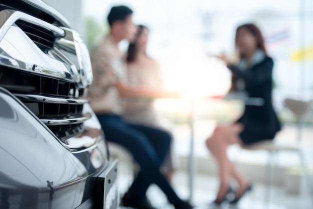 Размытие фона пары с удовольствием покупают новую машину в автосалоне и вступают в договор купи новую машину с автосалоном. концепция покупки автомобиля и концепция успеха