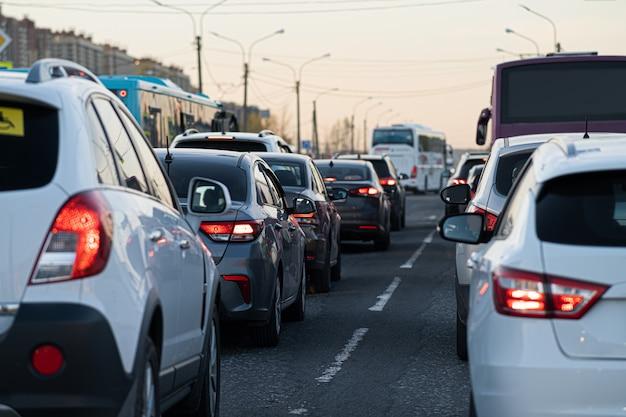 배경, 흐림, 초점 없음, 보케. 퇴근 후 출퇴근 시간에 교통 체증. 도시 이웃의 배경에 정지 된 자동차의 빨간 브레이크 등.