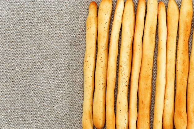 Background of breadsticks stacked in rows and sackcloth. top view on breadsticks. copycpase.