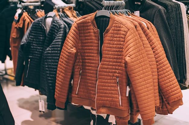 배경. 갈색과 검은 색 재킷이 슈퍼마켓의 옷걸이에 걸려 있습니다.