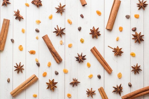 Background of cinnamon sticks, star anise, nuts and raisins on white wooden table.