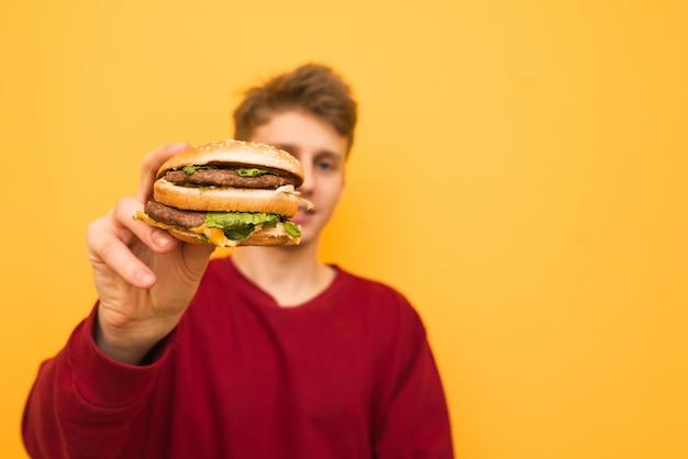 バックグラウンド。若い男の手でハンバーガーのクローズアップ。