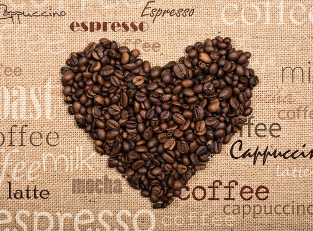 Background of coffee beans in a heart shape on burlap background
