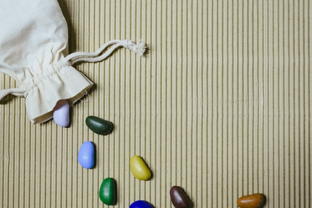 Background of colored fake stones scattered on a wavy paper with cloth sachet.