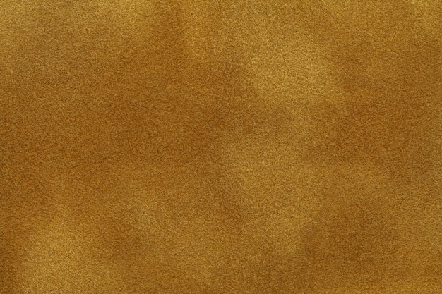 Background of dark golden suede fabric closeup. velvet matt texture of yellow nubuck textile