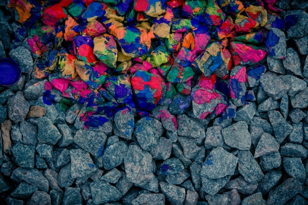 Background dark gray stones and rocks in colorful neon colors, view from above