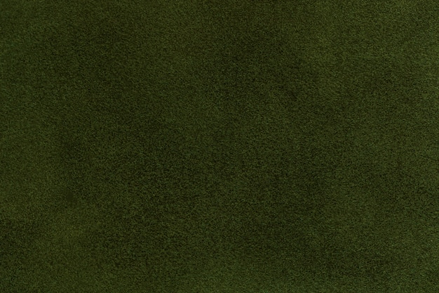 Background of dark green suede fabric closeup. velvet matt texture of olive nubuck textile