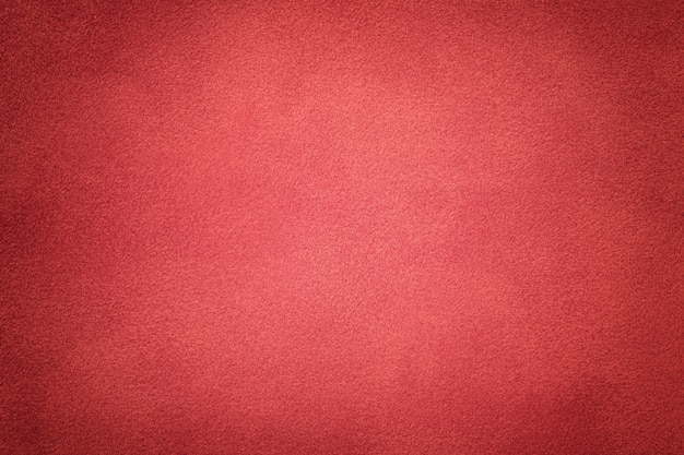 Background of dark red suede fabric closeup. velvet matte texture