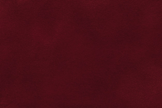 Background of dark red velvet textile, closeup