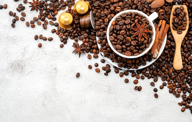 Background of dark roasted coffee beans and capsules with scoops setup on white concrete