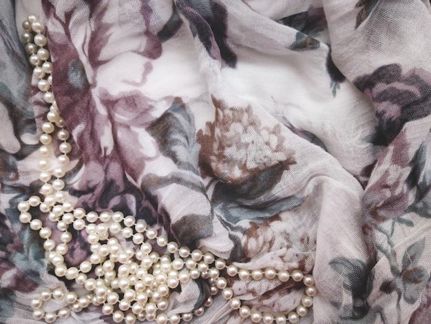 Фон нежная ткань светлая ткань с сиреневыми цветами, сложенными в складки, и белым жемчугом сбоку с пустым местом для надписи