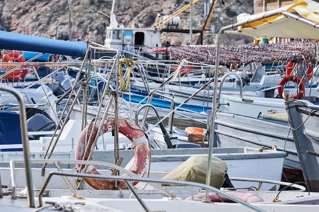Фон - детали конструкций различных прогулочных и развлекательных рыболовных судов, стоящих в гавани, сливаются друг с другом.