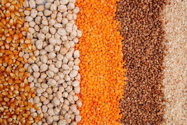 Background of different types of groats corn seeds chickpeas red lentils buckwheat and rice top view