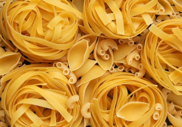 Background of diifferent types of raw italian pasta.