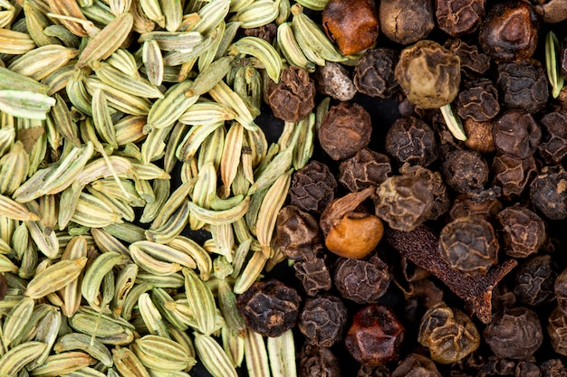 Priorità bassa dei semi di anice secchi con la vista superiore dei granelli di pepe