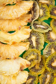 Background of dried fruits pineapple and kiwi slices top view