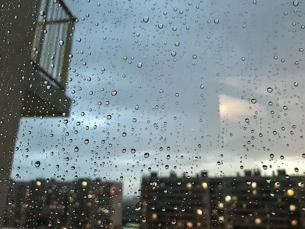 배경 물 방울입니다. 창틀에 빗방울입니다. 빗방울의 자연 패턴입니다. 비의 추상 샷 유리에 삭제합니다. 밤 도시와 창 밖 발코니입니다. 선택적 초점입니다. 텍스트 또는 로고를 위한 공간