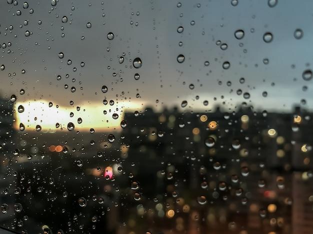 배경 물 방울입니다. 창틀에 빗방울입니다. 빗방울의 자연 패턴입니다. 비의 추상 샷 유리에 삭제합니다. 밤 도시와 창 밖 일몰입니다. 선택적 초점입니다. 텍스트 또는 로고를 위한 공간