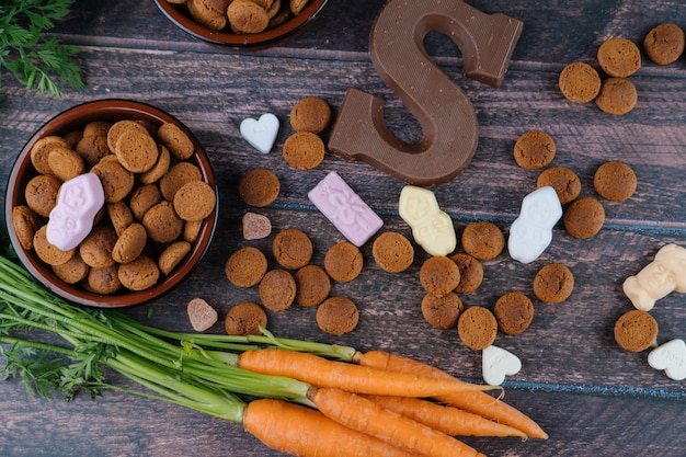 Background dutch holiday sinterklaaspepernoten, chocolate letter, sweets strooigoed and carrots for horse