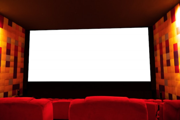 Background of empty cinema or theater hall with red seat and blank white screen for advertising.