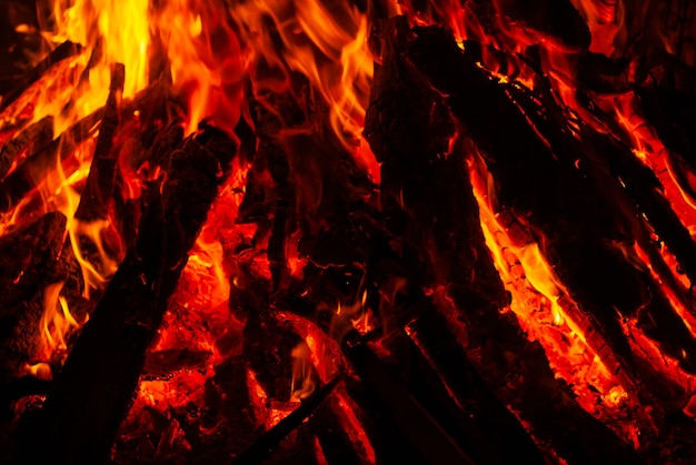 Background - flame over burning coals in the darkness