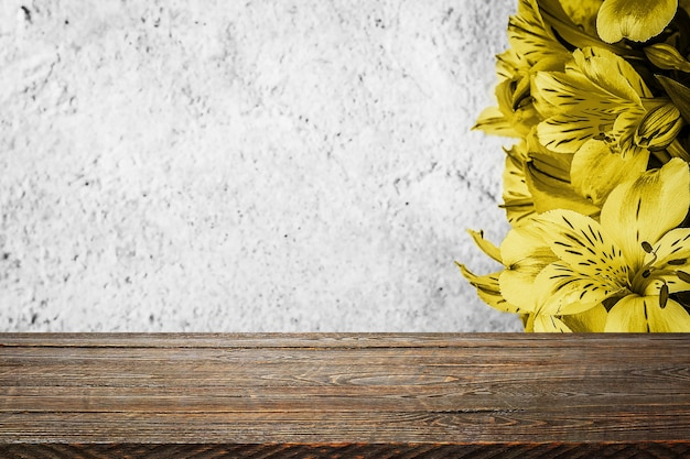 Background flowers on a textured stucco wall and blank wooden planks in the foreground