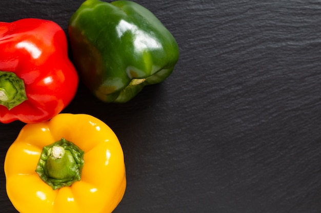 Background for food product 3 colors red green and yellow of organic bell pepper or parpika on black slate board