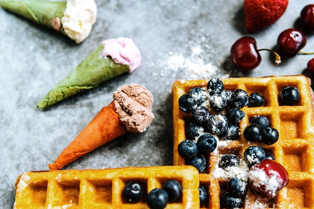 Background of foods refreshing ice cream in cones with red fruits and waffles