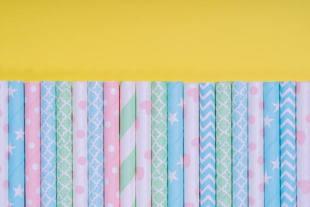 노란색 배경에 고립 된 종이 튜브와 배너에 대 한 배경. 칵테일 튜브가 있는 배너용 프레임입니다. 파티 배너, 칵테일 바. 우아한 종이 마시는 빨대. 클로즈업, 복사 공간