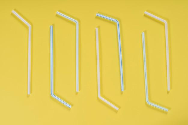 노란색 배경에 격리된 플라스틱 튜브가 있는 배너의 배경입니다. 칵테일 튜브가 있는 배너용 프레임입니다. 파티 배너, 칵테일 바. 우아한 종이 마시는 빨대. 클로즈업, 복사 공간