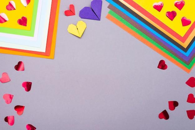 創造性の背景。色紙と紙のハート。紙を切り取ります。