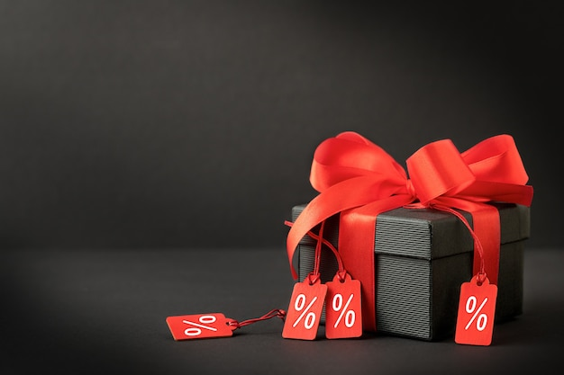 赤いリボンとラベルが付いた黒いギフトボックスの販売の背景