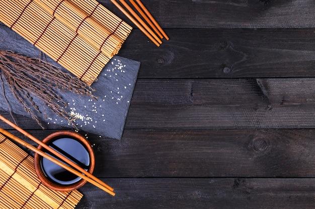 Фон для суши. бамбуковая циновка и соевый соус на черном деревянном столе. вид сверху с копией пространства