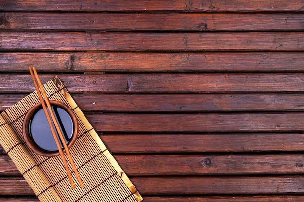 寿司の背景。竹マット、醤油、木製のテーブルには箸。トップビューとコピースペース