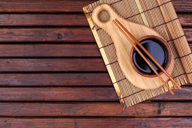 Фон для суши. бамбуковая циновка, соевый соус, палочки для еды на деревянном столе. вид сверху и копировать пространство