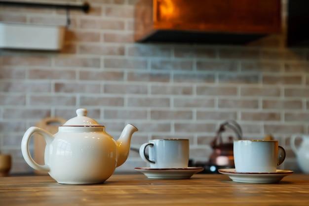 居心地の良い家のキッチンエリアのインテリアでのお茶の儀式の背景。マグカップ付きのティーポットがテーブルの上にあり、ゲストとお茶を待っています。家の快適さとリラクゼーションの概念。コピースペース