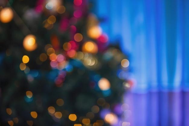디자이너에 대한 배경입니다. 크리스마스 트리에 흐릿한 여러 가지 빛깔의 조명입니다.