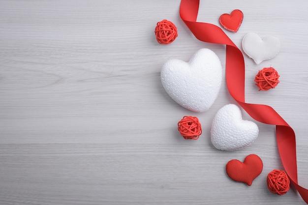 Фон для поздравительной открытки дня святого валентина. концепция дня святого валентина. красные подарочные ленты, подарки, сердца на деревянном фоне. вид сверху.