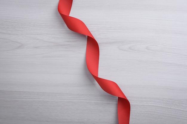 バレンタインデーのグリーティングカードの背景。バレンタインデーのコンセプト。赤いギフトリボン、ギフト、木製の背景にハート。上面図。