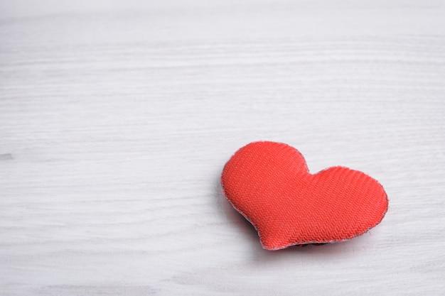バレンタインデーのグリーティングカードの背景。バレンタインデーのコンセプト。木製の背景に赤いハート。
