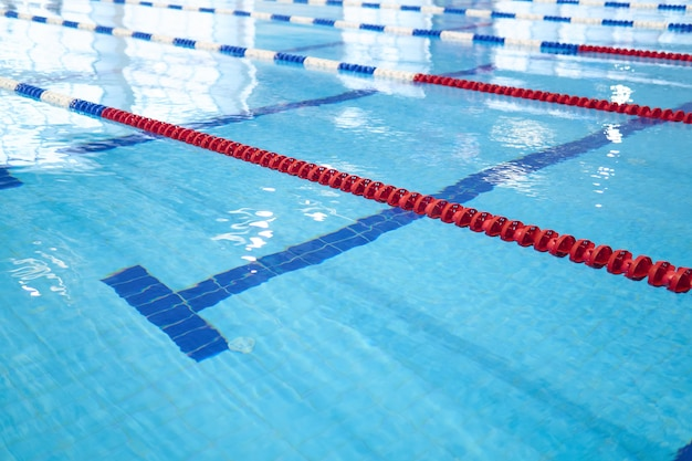 Background - fragment of the competition pool with blue water and marked swimming lanes