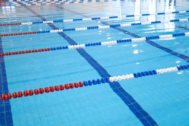 На заднем плане - фрагмент соревновательного бассейна с голубой водой и размеченными дорожками для плавания.