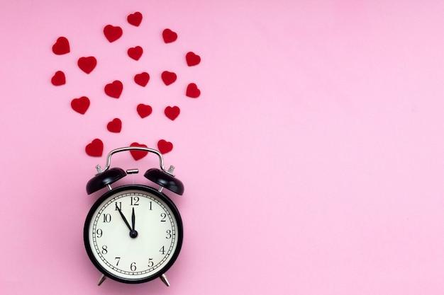 ピンクの背景に黒い目覚まし時計とその周りの赤いハートの背景
