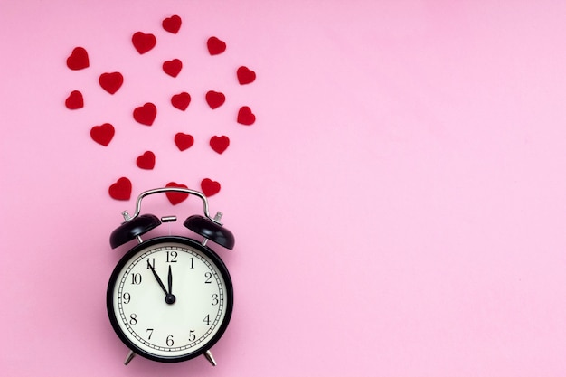 Background from a black alarm clock and red hearts around it on a pink background