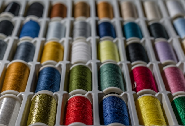 Background from bobbins with multicolored thread for sewing